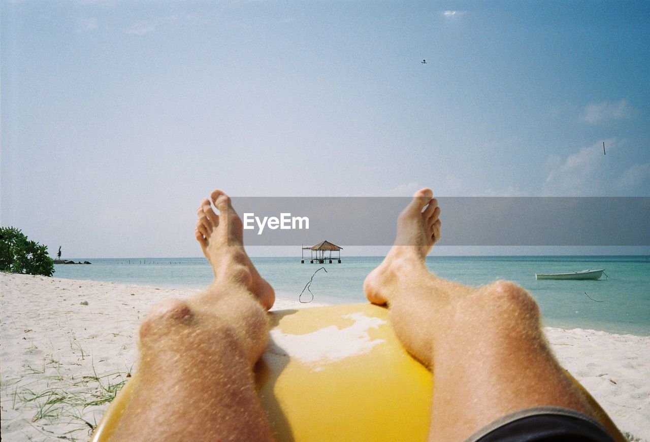 Low section of man relaxing at beach against sky during summer