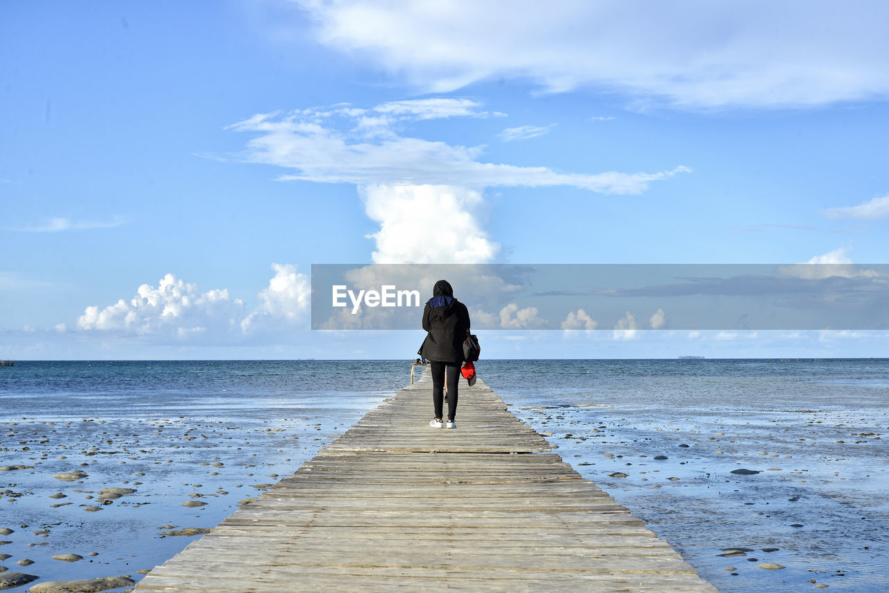 Rear view of woman standing on pier at beach against sky