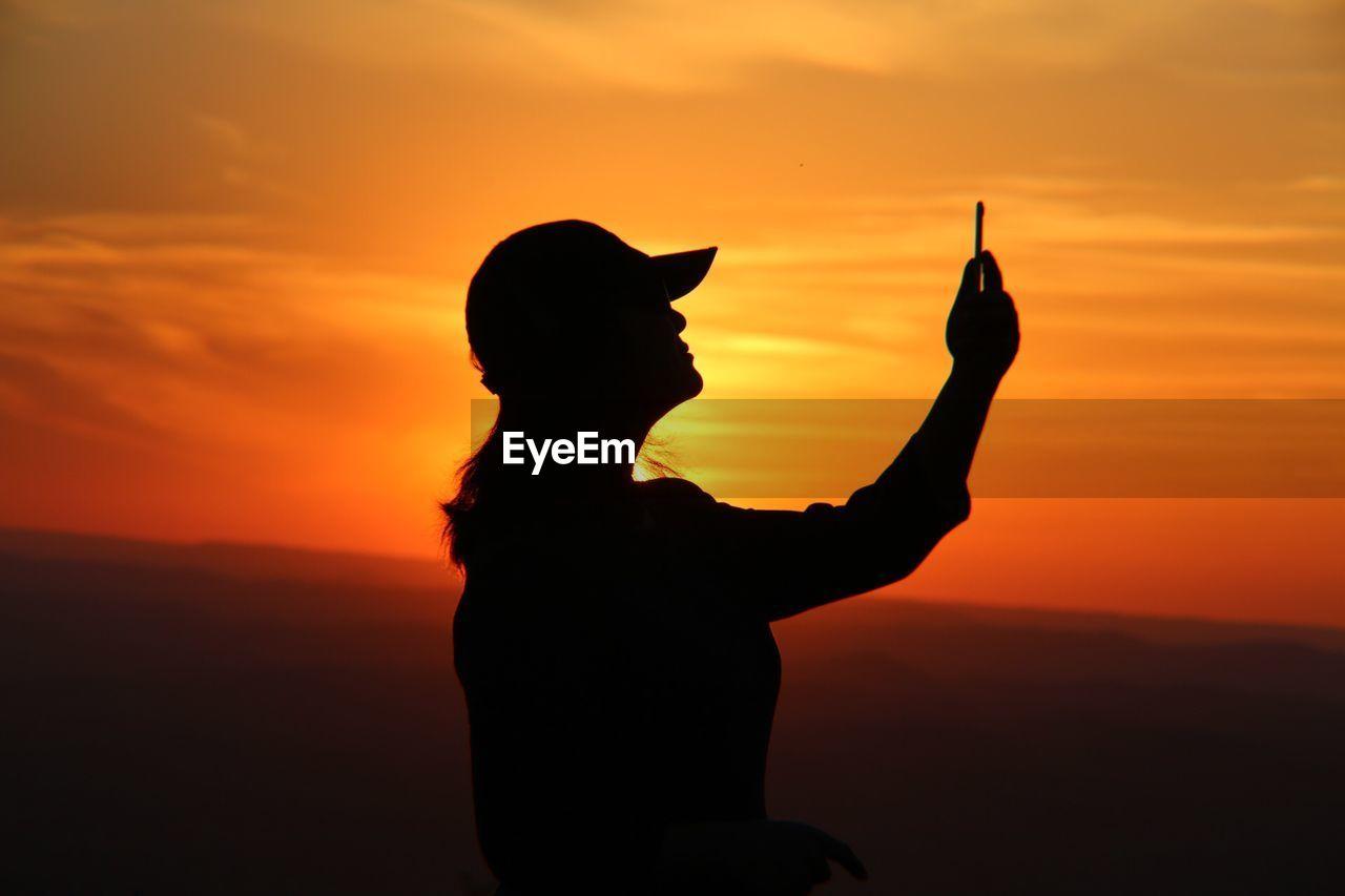 Silhouette woman taking selfie against orange sky during sunset