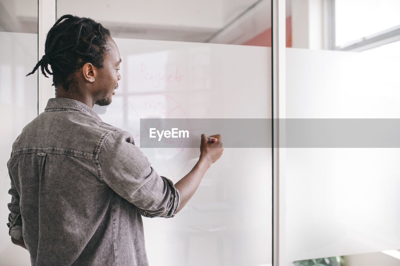 Side View Of Businessman Writing On Board In Office