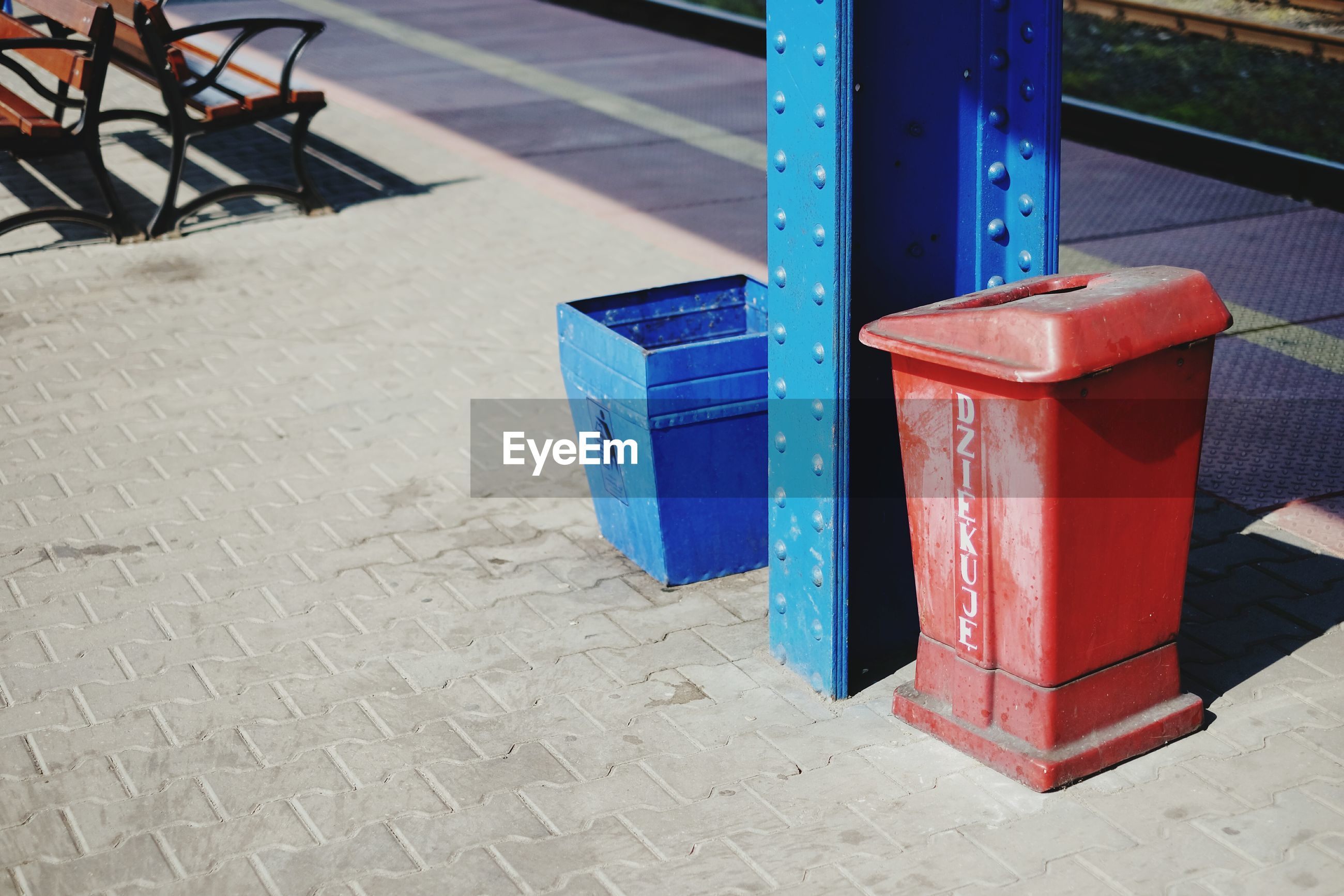 Garbage bins by pillar at railroad station platform