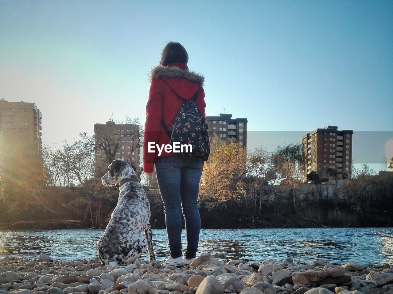 Rear View Of Woman With Dog Standing On Rocky Riverbank