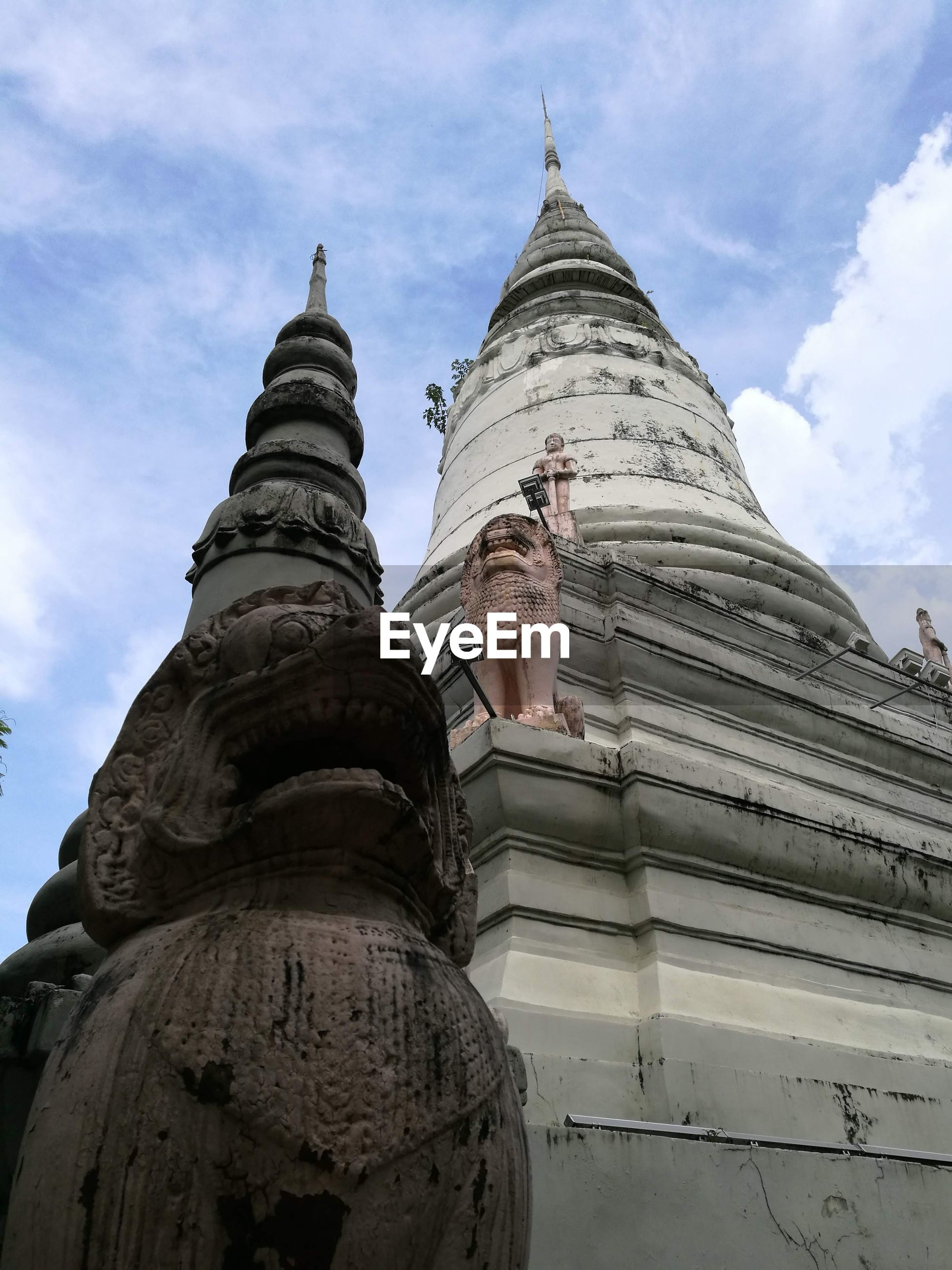 Low angle view of statue on temple building against sky