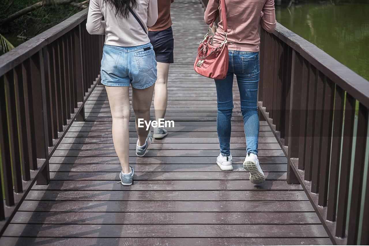 Low section of friends walking on footbridge
