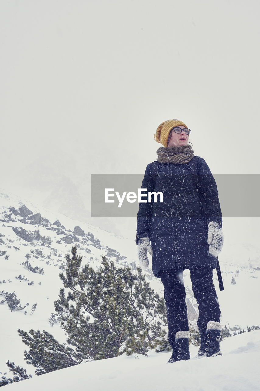 Low angle view of woman standing against sky during winter