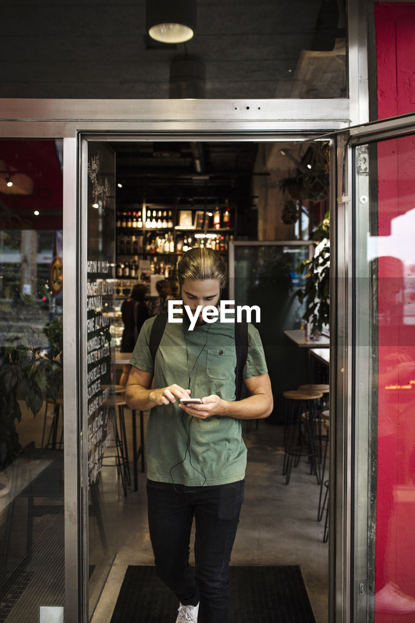 one person, front view, real people, business, standing, store, small business, occupation, indoors, young adult, three quarter length, window, food and drink, glass - material, casual clothing, men, retail, lifestyles, entrepreneur