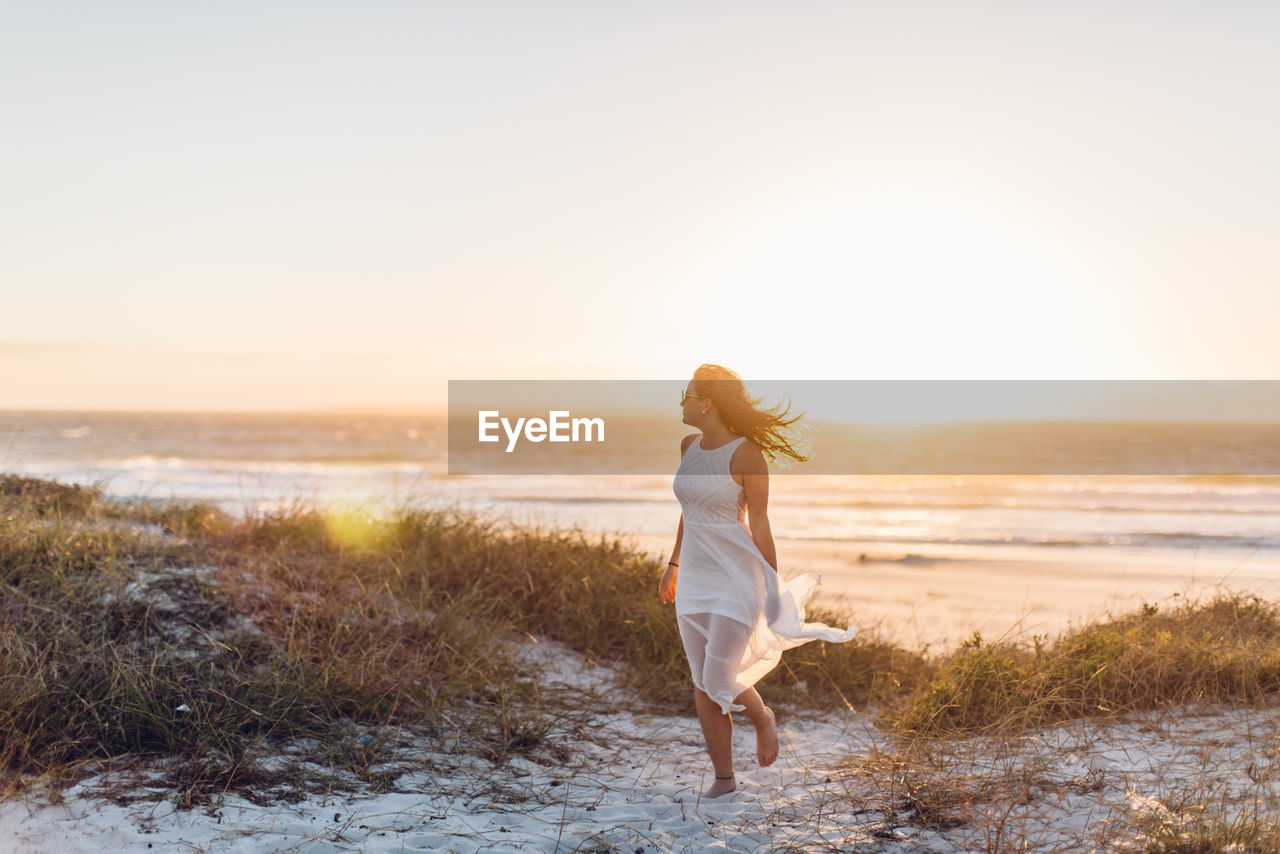 Young Woman Walking At Beach Against Clear Sky During Sunset