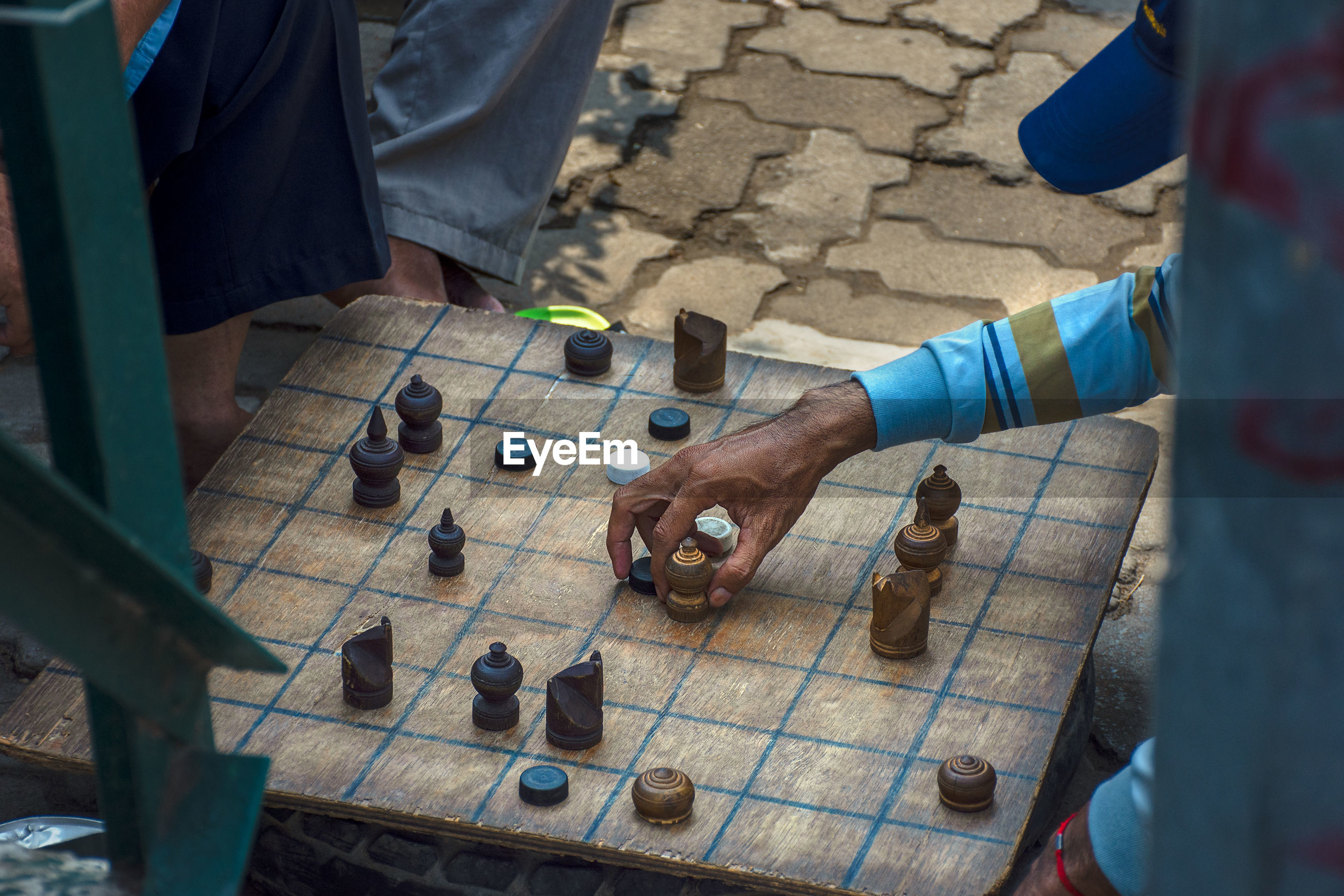 Friends playing board game on footpath