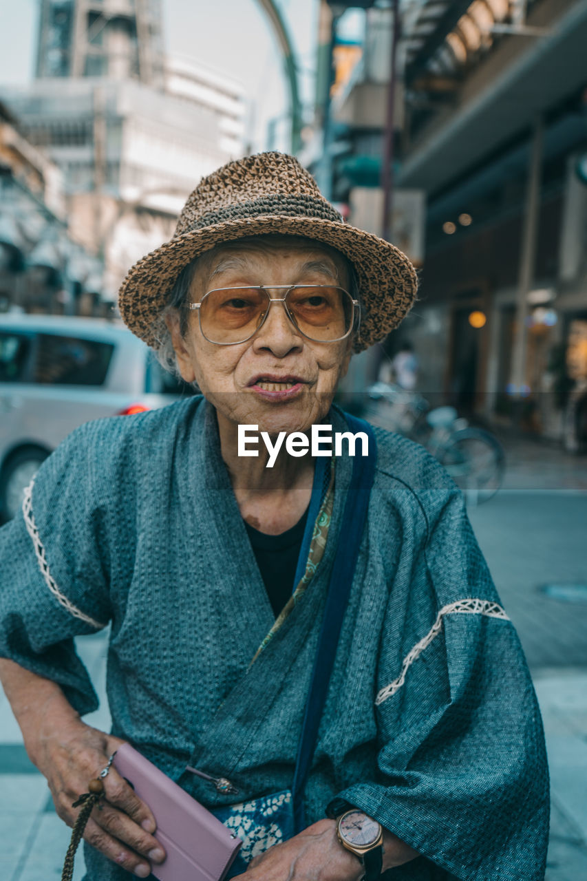 real people, front view, one person, hat, clothing, portrait, city, lifestyles, architecture, focus on foreground, leisure activity, adult, senior adult, looking at camera, waist up, mobile phone, technology, casual clothing, wireless technology, outdoors, warm clothing, mature men