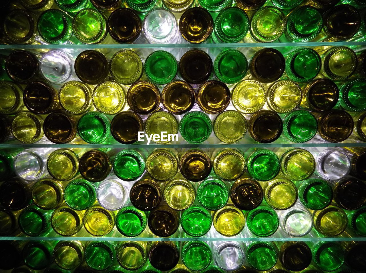 green color, full frame, backgrounds, glass - material, abundance, bottle, no people, large group of objects, container, indoors, multi colored, close-up, pattern, still life, geometric shape, shape, transparent, arrangement, circle, refreshment, glass
