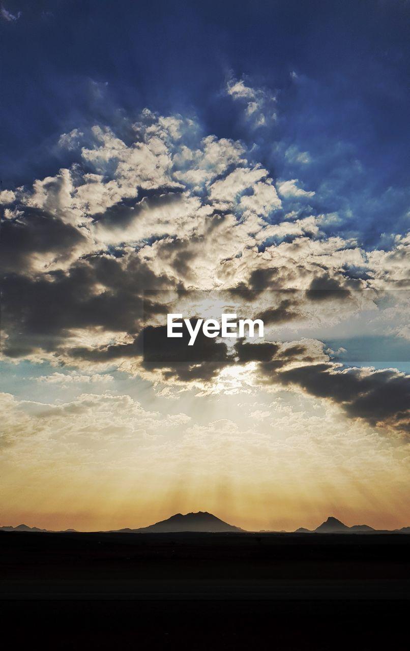 sky, cloud - sky, beauty in nature, silhouette, scenics - nature, tranquil scene, sunset, tranquility, nature, no people, environment, landscape, non-urban scene, idyllic, sunlight, mountain, outdoors, horizon, sunbeam, dramatic sky