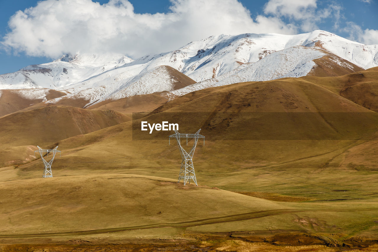 Pylons of high-voltage power lines in the mountains, snowy mountain peaks and blue sky
