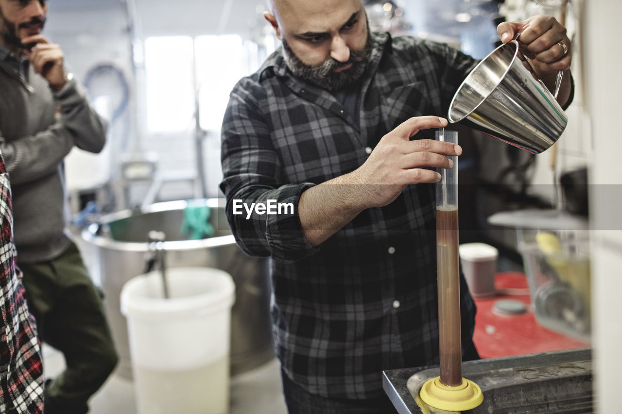 Coworkers looking at man pouring beer in container at brewery