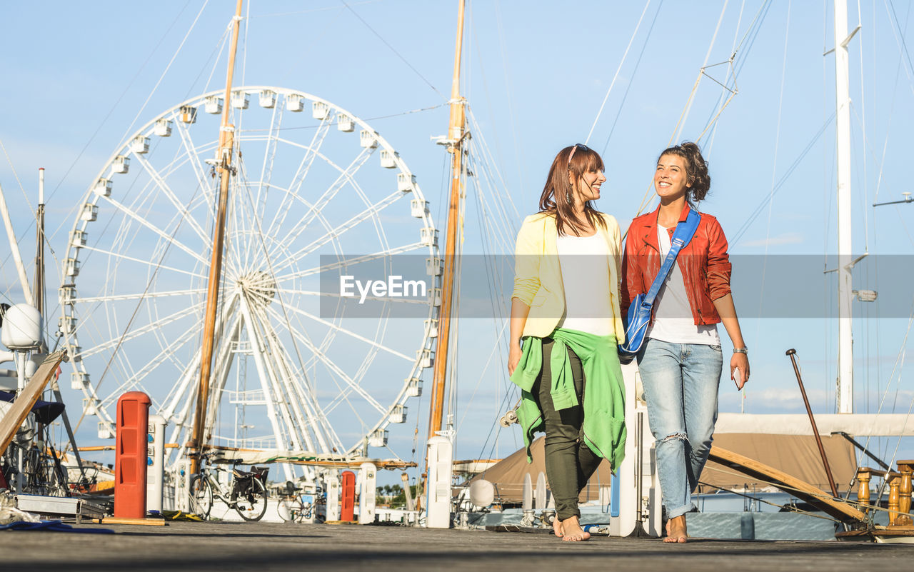 two people, amusement park ride, togetherness, leisure activity, amusement park, real people, couple - relationship, sky, full length, ferris wheel, arts culture and entertainment, young adult, young men, casual clothing, lifestyles, heterosexual couple, men, women, front view, young women, positive emotion, outdoors