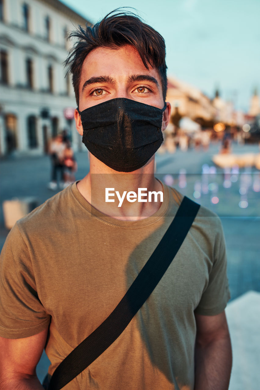 Young man standing in the city center in the evening, looking away, wearing the face mask