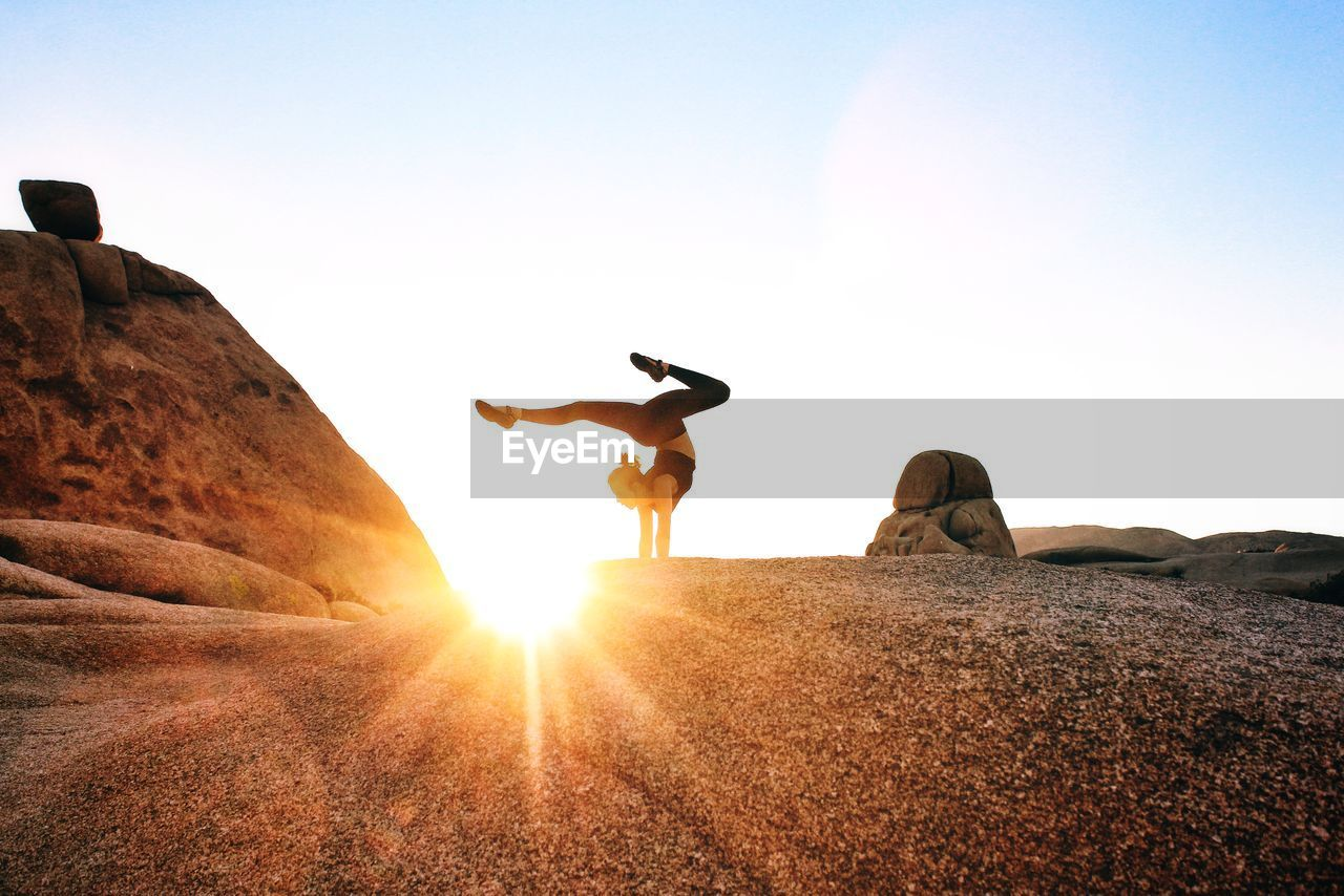 Full Length Of Woman Practicing Yoga Against Clear Sky During Sunset