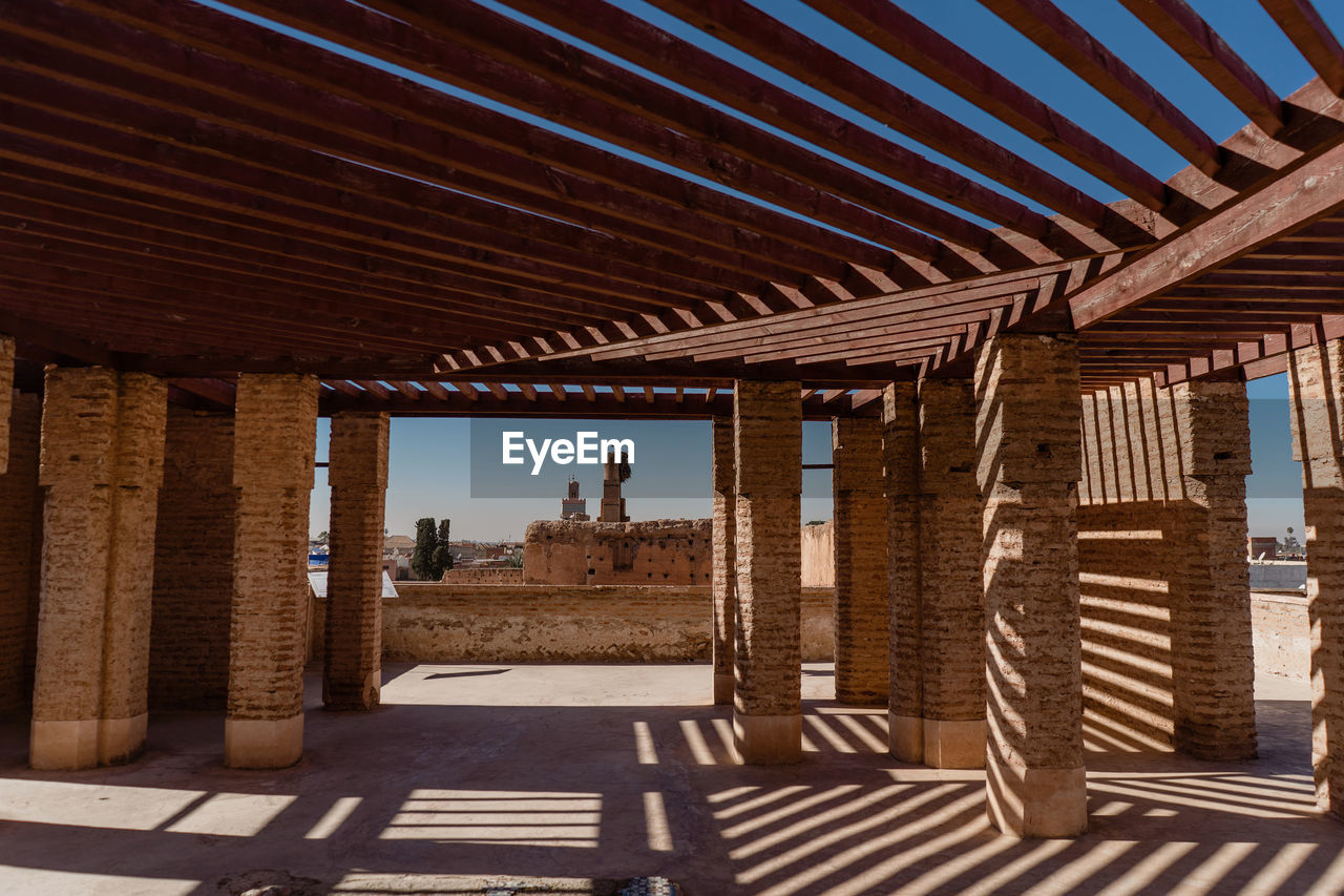 architecture, built structure, sunlight, nature, day, indoors, shadow, real people, one person, pattern, lifestyles, architectural column, building, sky, wood - material, men, roof, ceiling