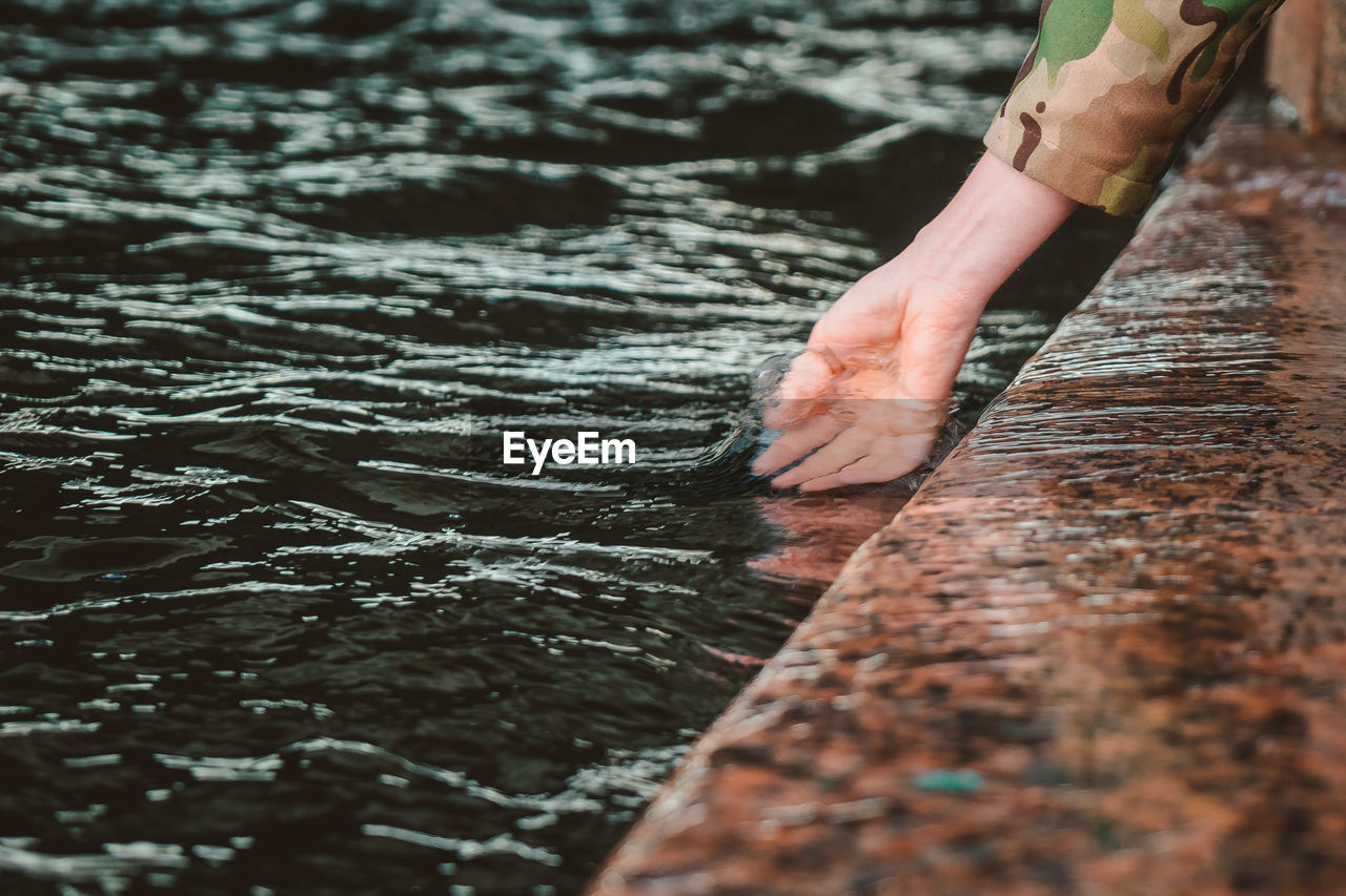 The girl dipped her hand into the water. touching the river with the palm of your hand