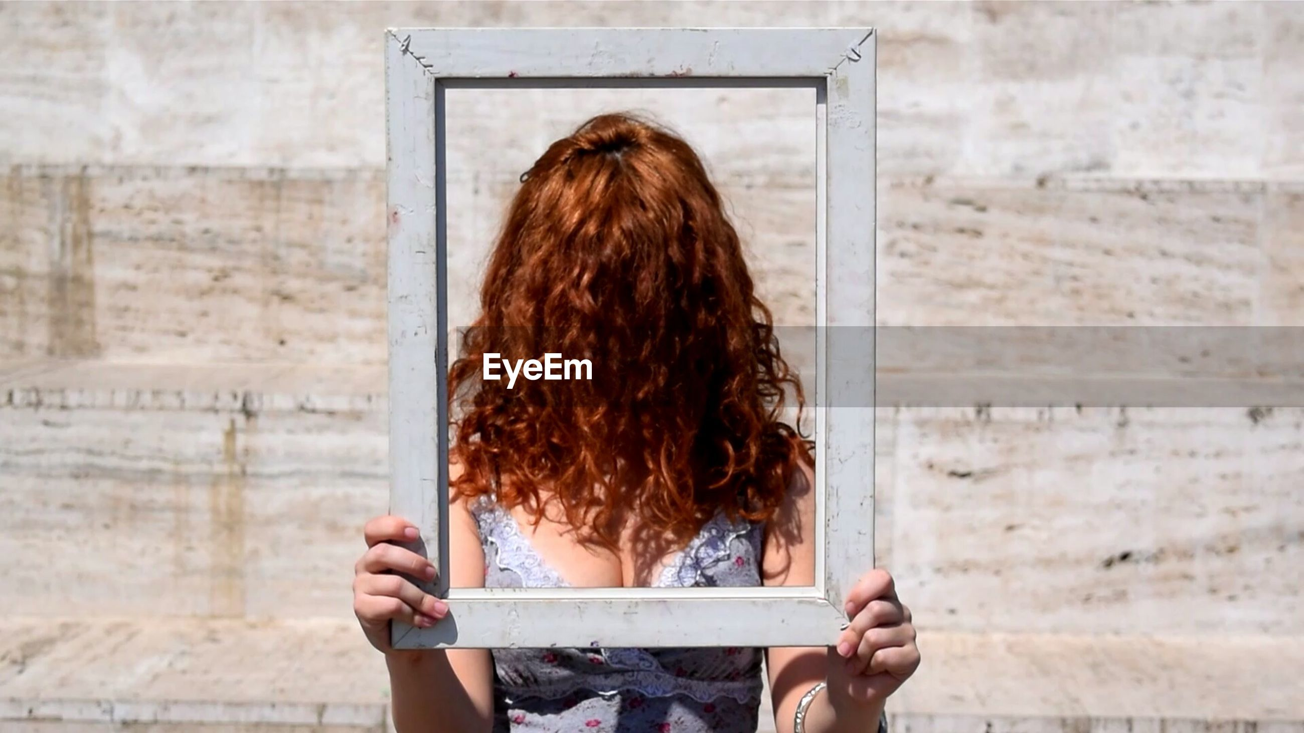 Woman with face covered in hair holding picture frame