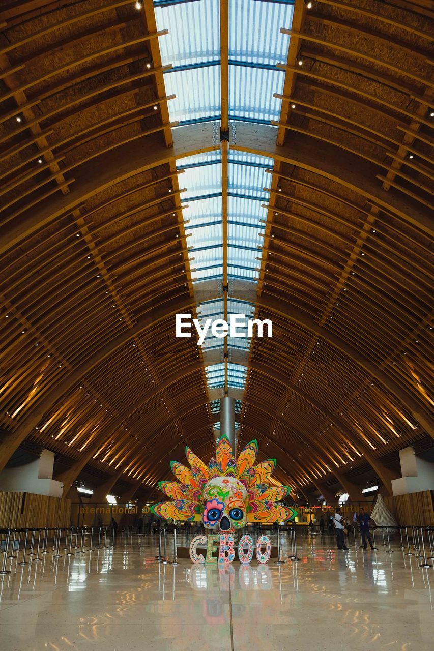 indoors, ceiling, architecture, built structure, lighting equipment, incidental people, amusement park, multi colored, day, pattern, illuminated, roof, flooring, empty, amusement park ride, architectural column, hanging, design