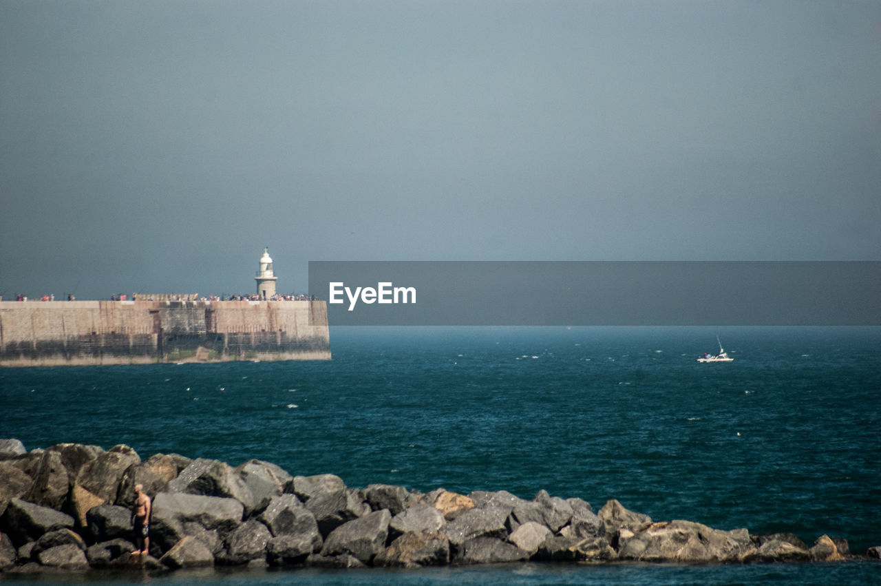 sea, water, architecture, sky, built structure, rock, rock - object, solid, lighthouse, building exterior, nature, tower, scenics - nature, guidance, horizon over water, beauty in nature, no people, copy space, horizon, outdoors, sailboat, groyne