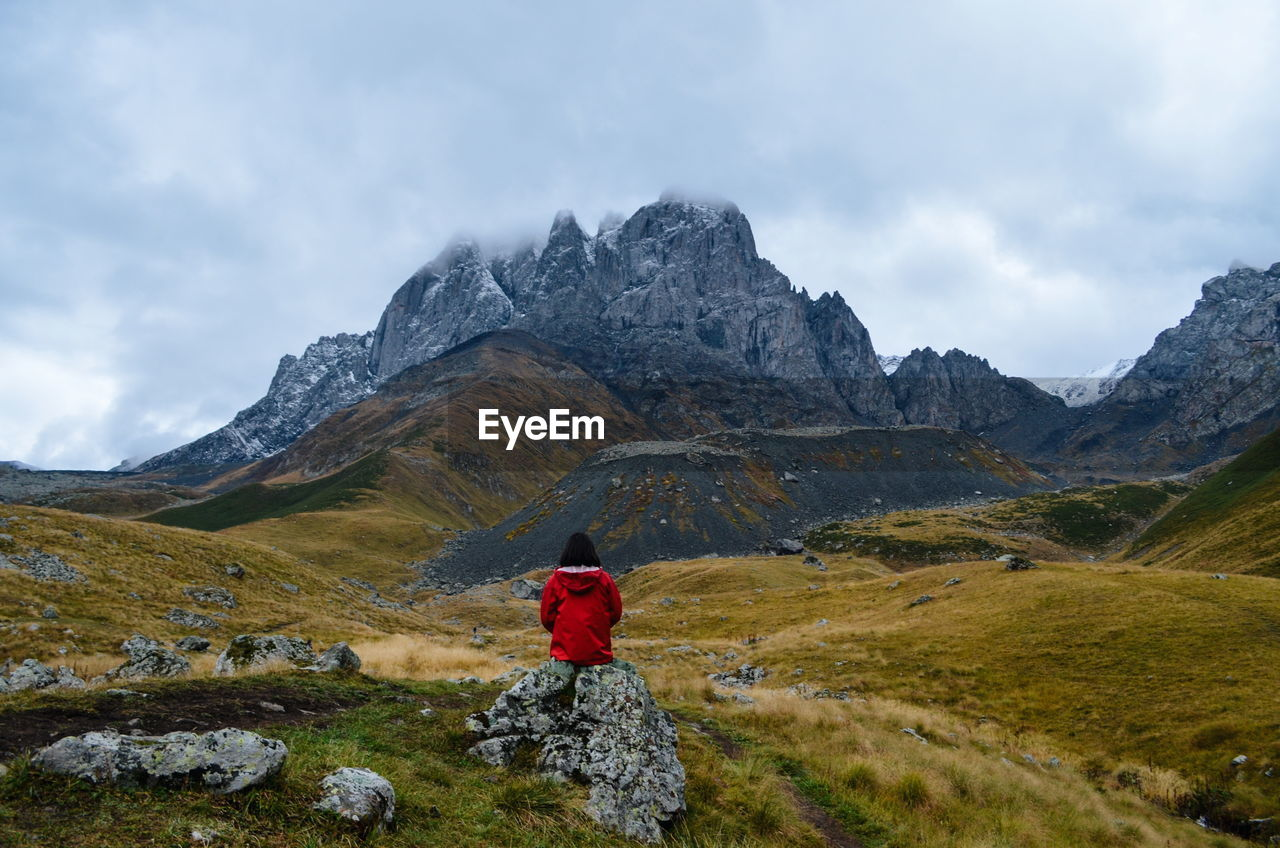 mountain, sky, rear view, cloud - sky, one person, beauty in nature, leisure activity, scenics - nature, real people, lifestyles, non-urban scene, nature, mountain range, day, tranquil scene, adventure, tranquility, standing, women, outdoors, hood - clothing