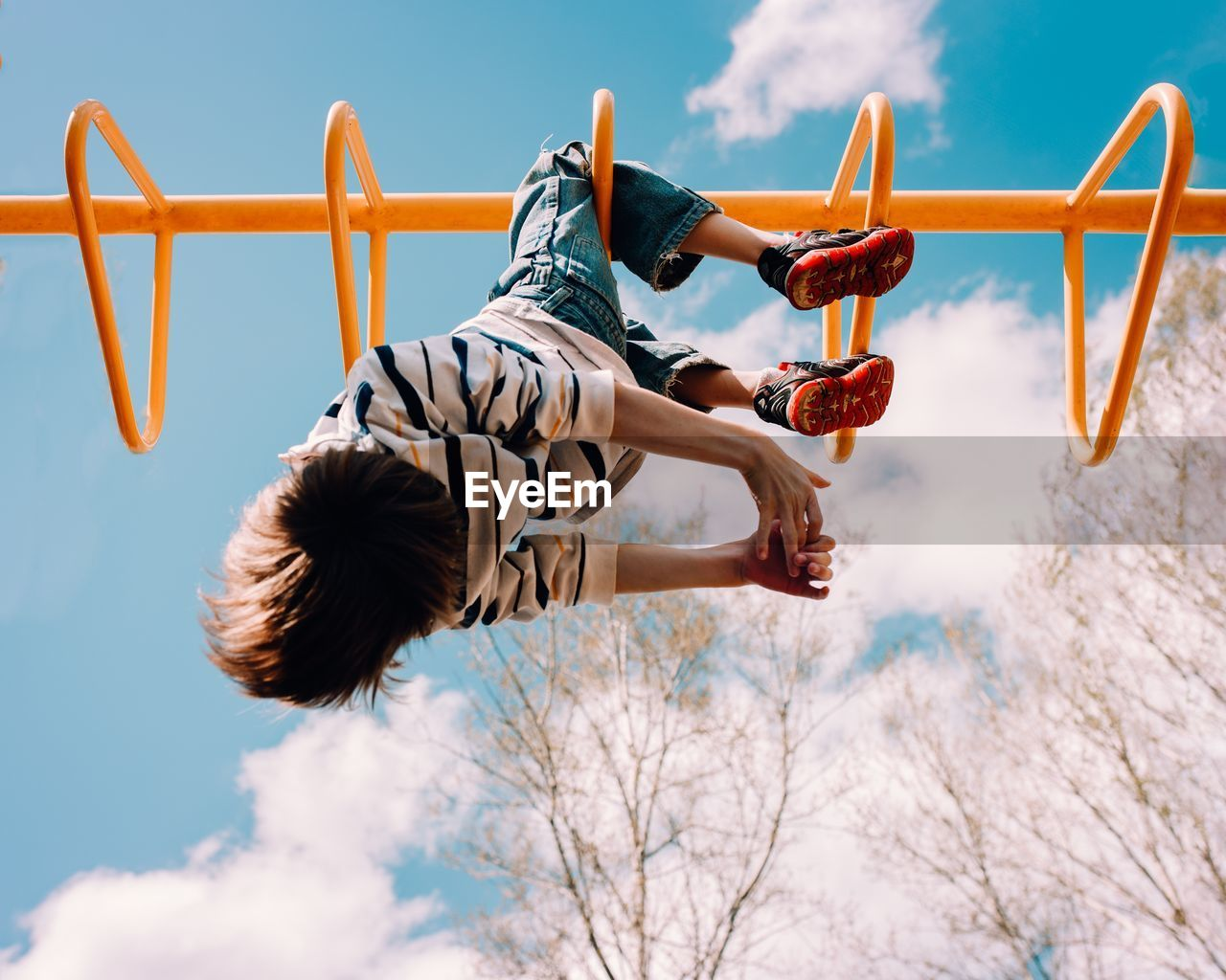 Low angle view of boy playing on monkey bars against sky