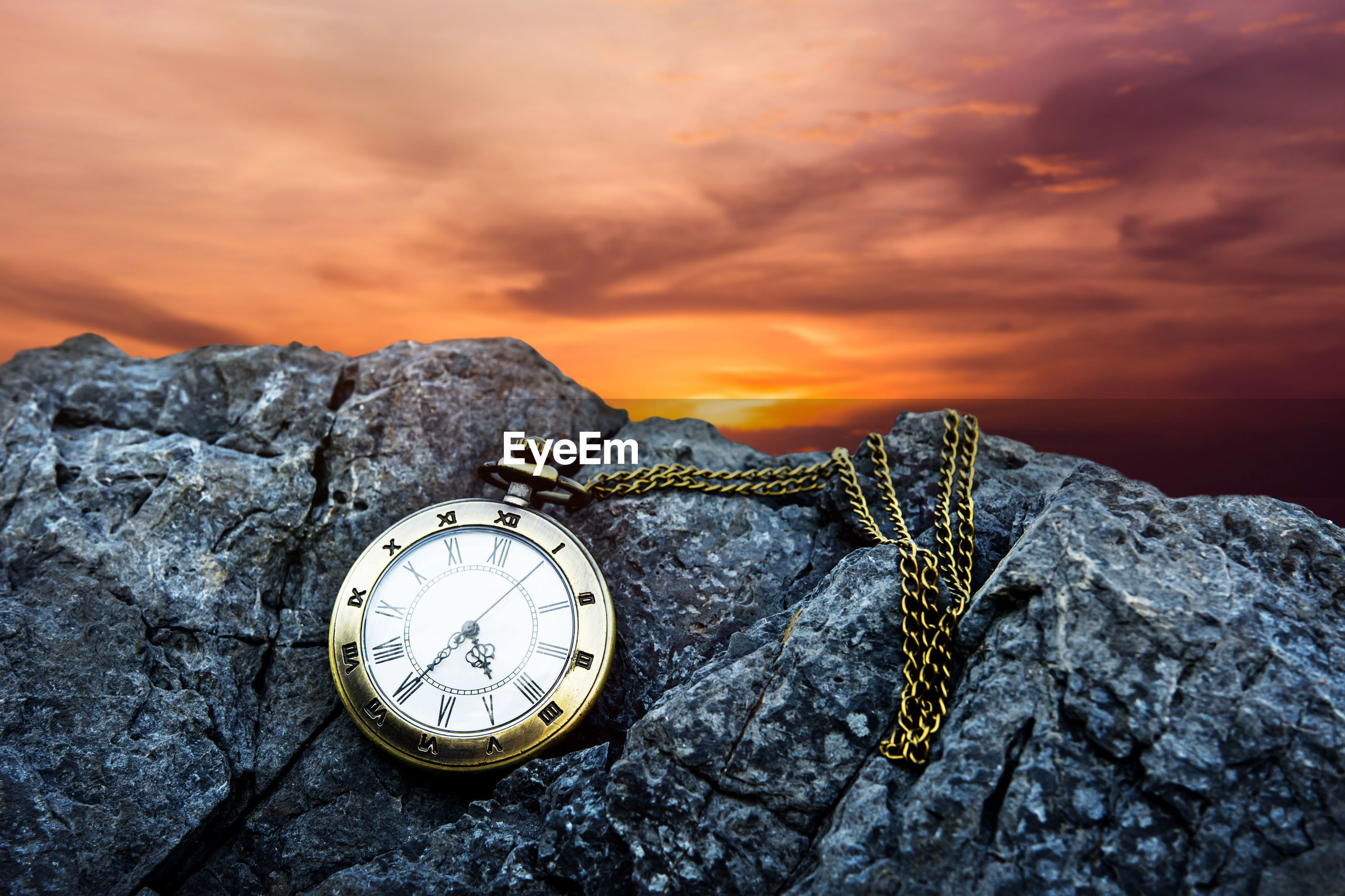 Close-up of pocket watch on rock against sky during sunset