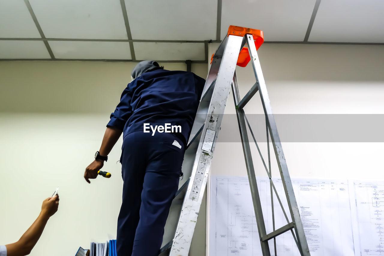 Rear view of man repairing ceiling