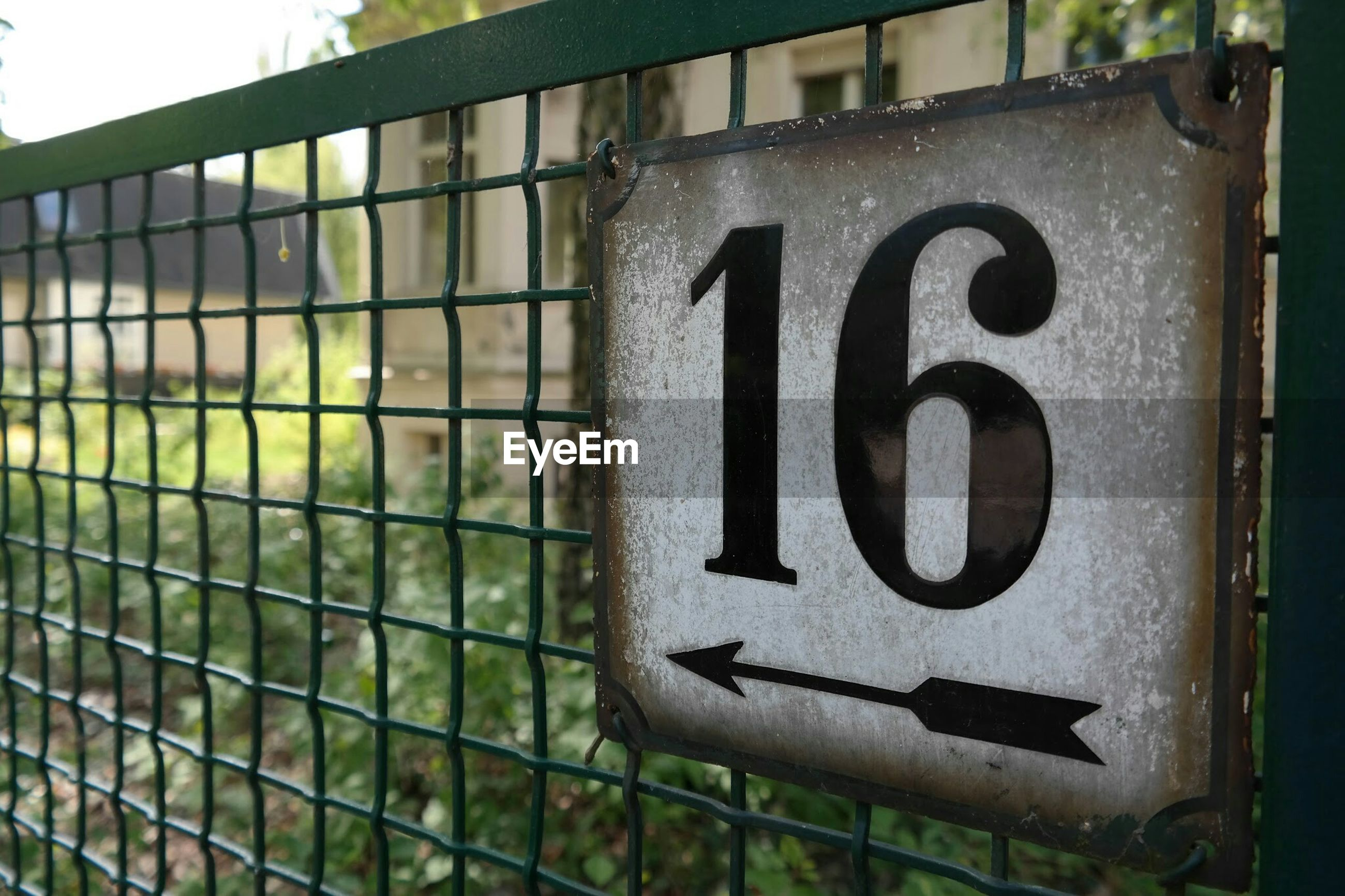 Close-up of number 15 and arrow symbol on fence