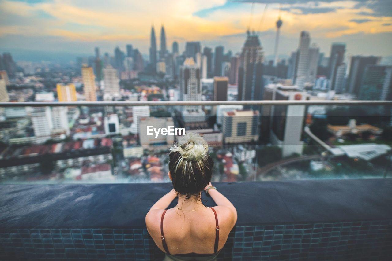 REAR VIEW OF WOMAN LOOKING AT KUALA LUMPUR CITY VIEW