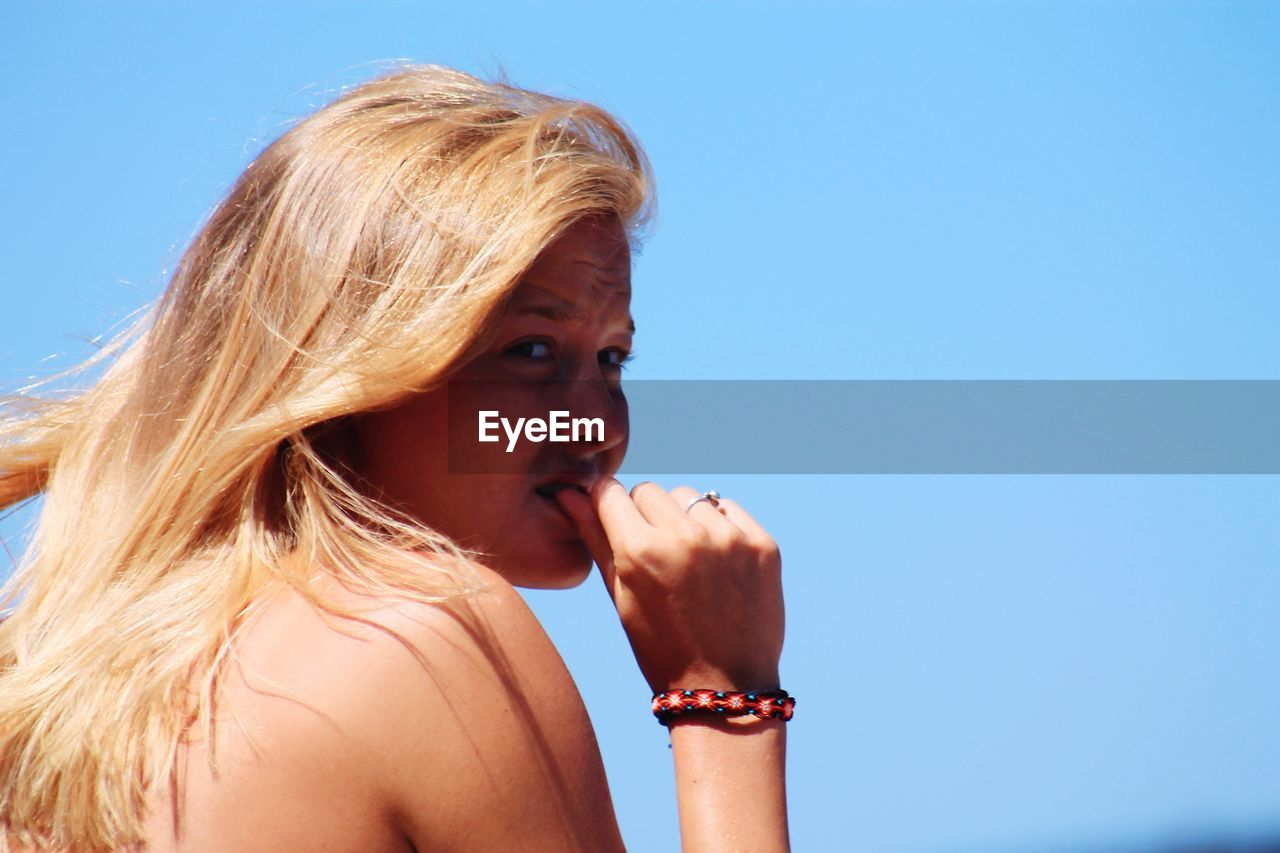 Young Woman Nail Biting While Looking Away Against Clear Blue Sky