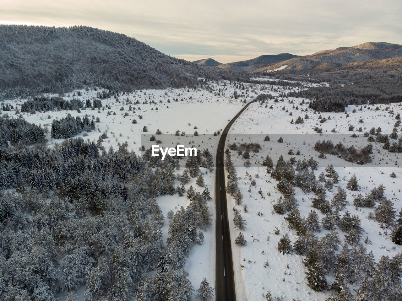Aerial view of the road during winter with snow on dusk. lika, croatia