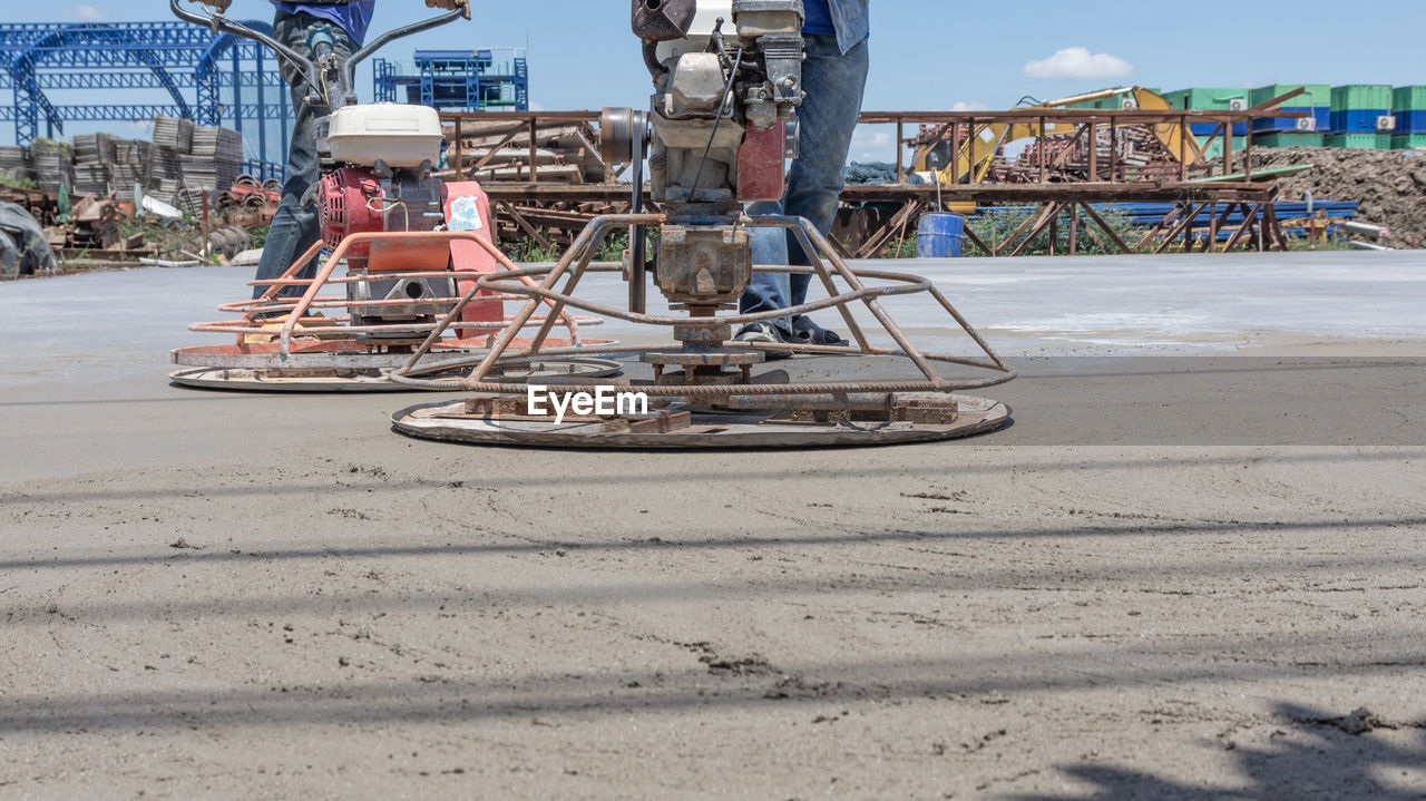 day, architecture, transportation, men, nature, incidental people, beach, water, sand, sky, mode of transportation, land, built structure, outdoors, group of people, adult, real people, sea, construction industry, nautical vessel
