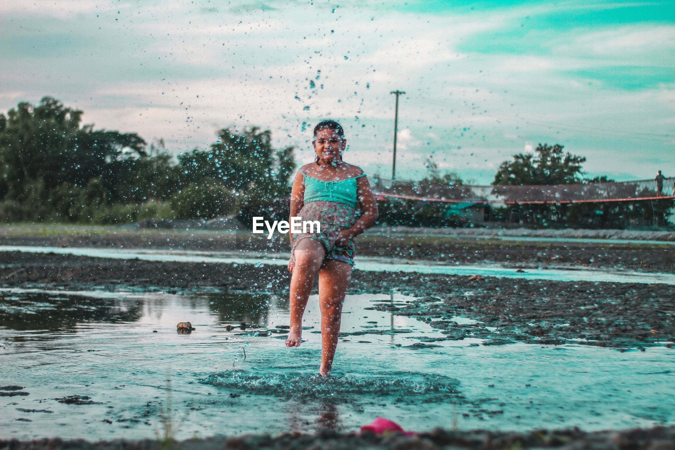 Full length of girl splashing water while standing in puddle against sky