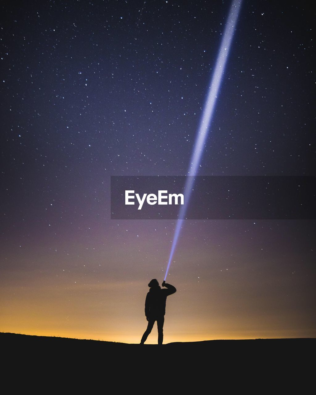 Silhouette Man With Illuminated Flashlight Against Star Field