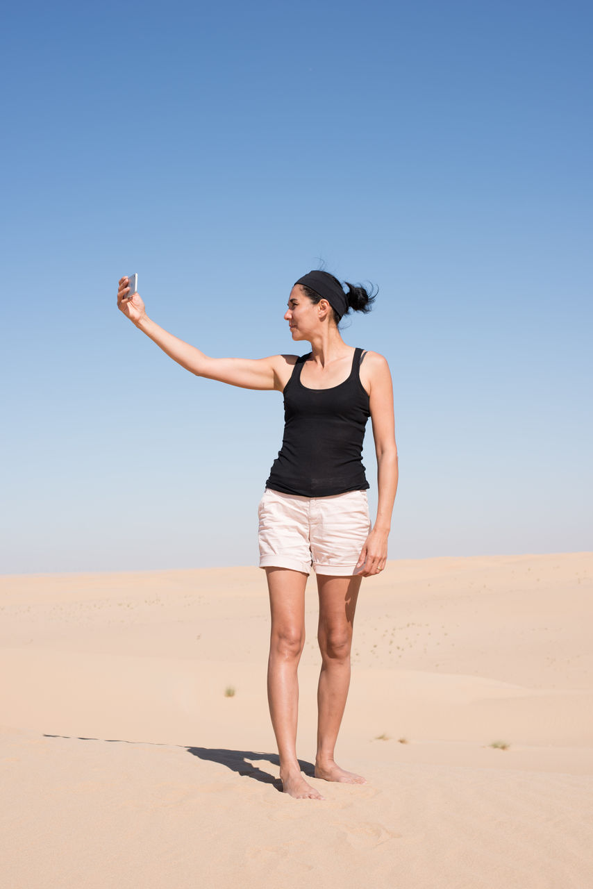 Full Length Of Woman Taking Selfie At Beach Against Clear Sky