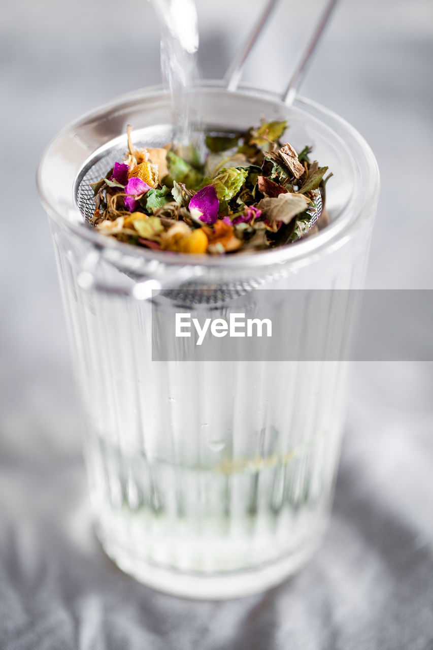 HIGH ANGLE VIEW OF ICE CREAM IN GLASS CONTAINER ON TABLE