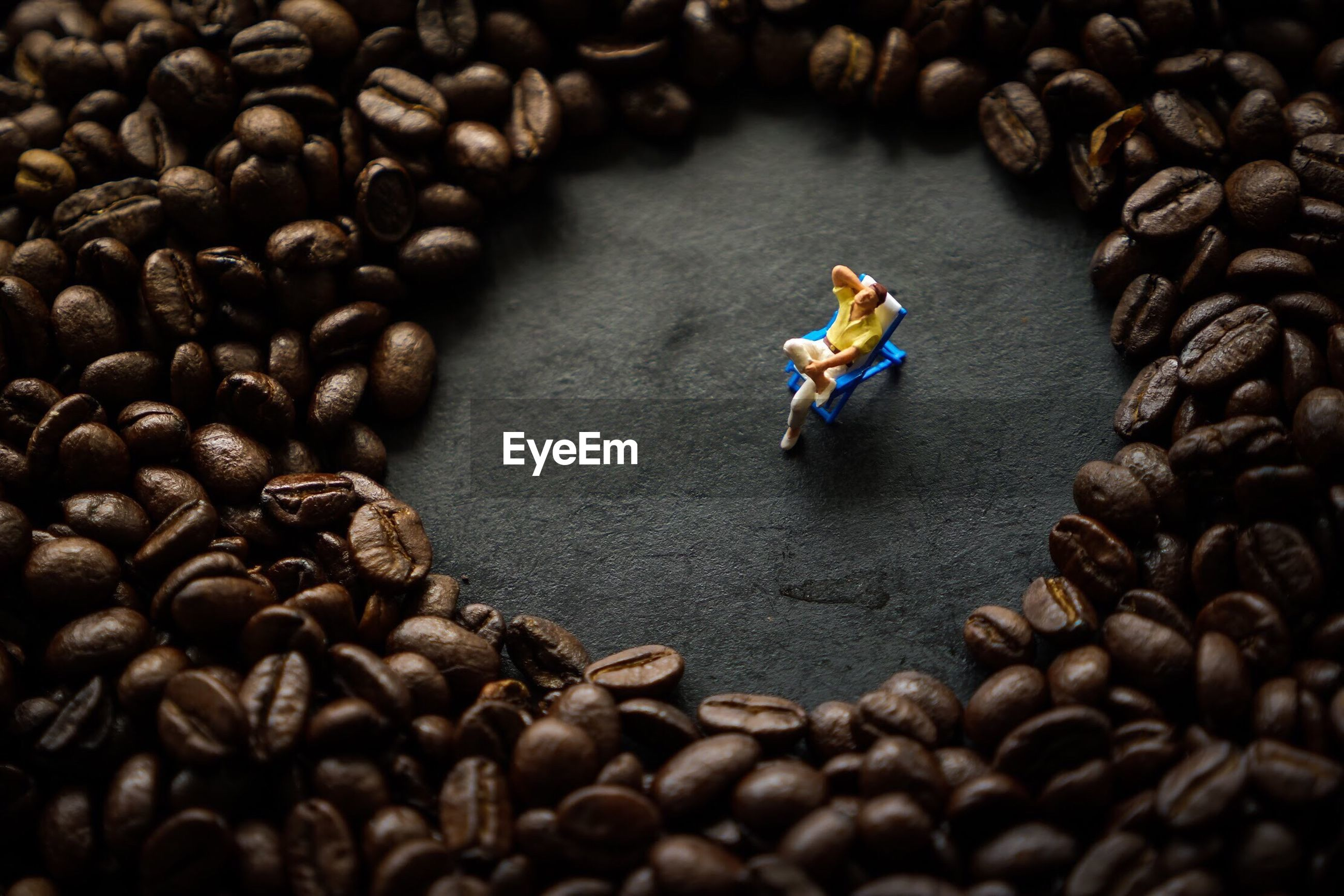 High angle view of figurine amidst coffee beans on table