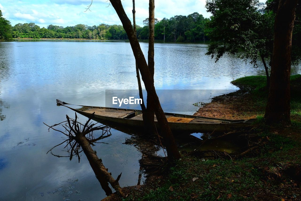 water, tree, nature, lake, beauty in nature, tranquility, reflection, scenics, tranquil scene, nautical vessel, outdoors, no people, moored, sky, transportation, day, growth, tree trunk, dead tree