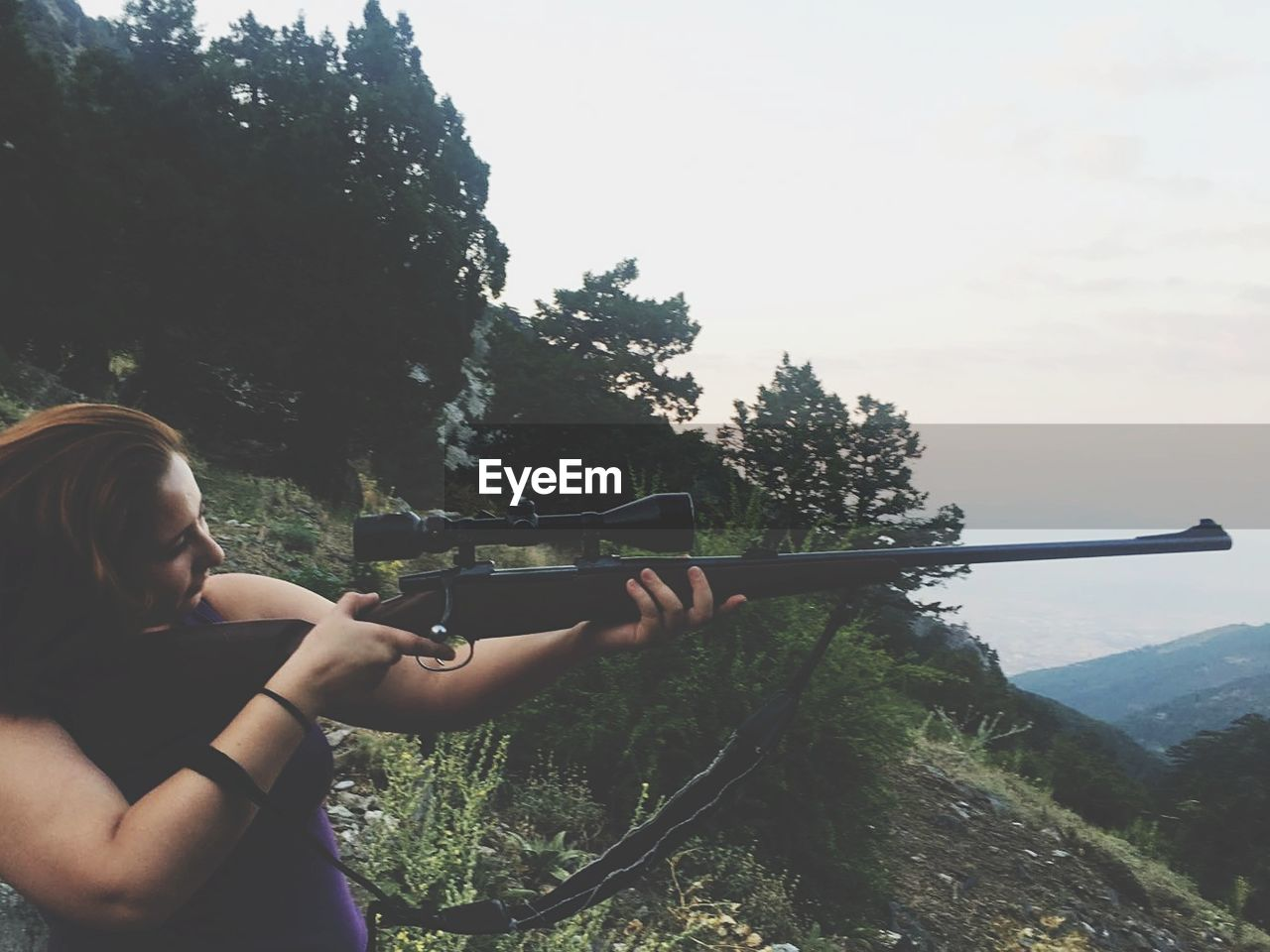 Woman Aiming Riffle While Standing In Forest
