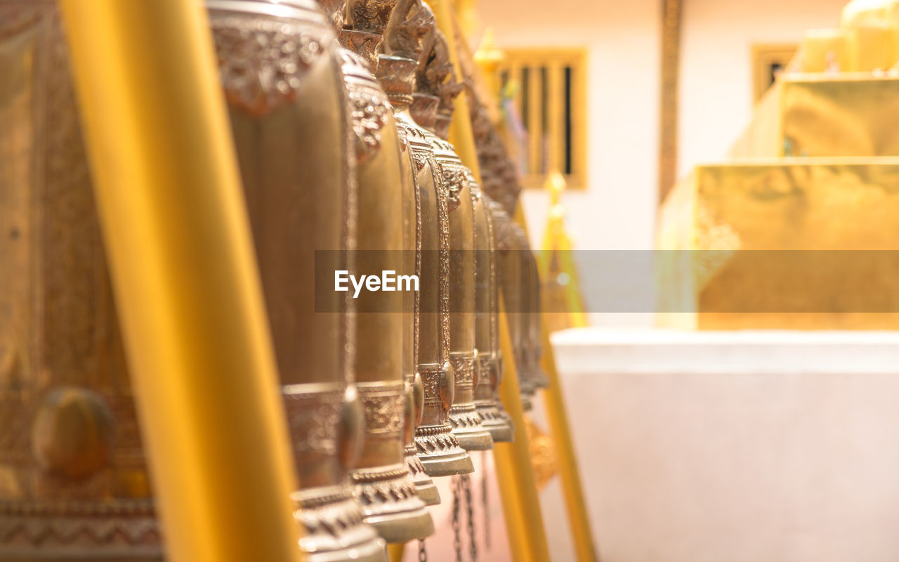selective focus, indoors, no people, architecture, in a row, built structure, close-up, large group of objects, yellow, metal, day, building, business, food and drink, still life, place of worship, brown, arts culture and entertainment, shelf, silver colored