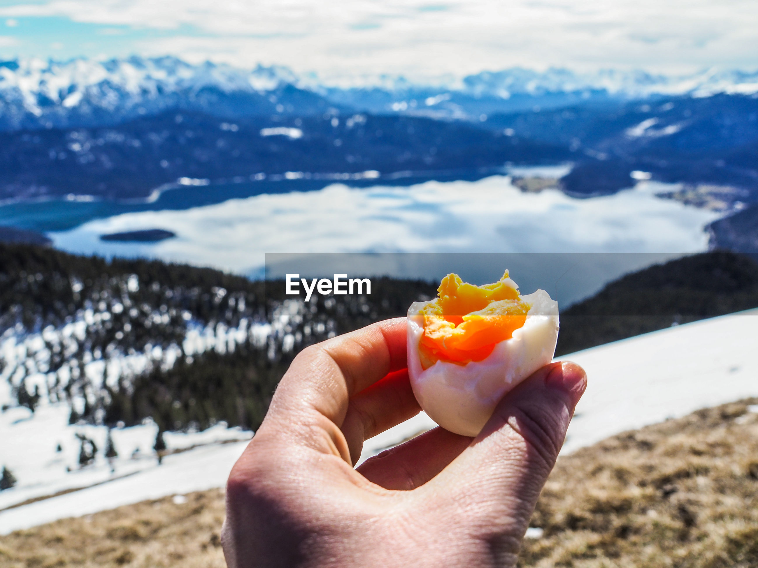 Close-up of hand having boiled egg against lake and snowcapped mountains