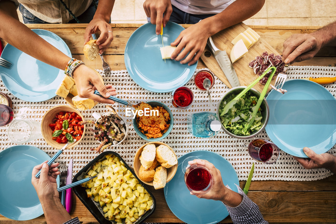 food and drink, food, group of people, table, togetherness, real people, men, plate, women, lifestyles, human hand, high angle view, hand, bowl, bonding, drink, human body part, healthy eating, freshness, friendship, meal, glass
