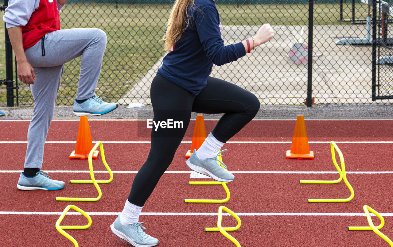 Low section of woman running over hurdles at sports track
