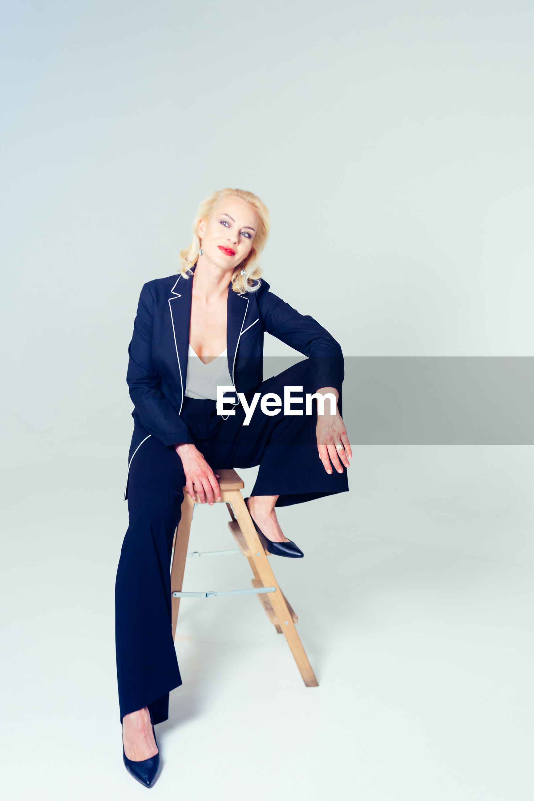 Smiling businesswoman sitting on stool against white background