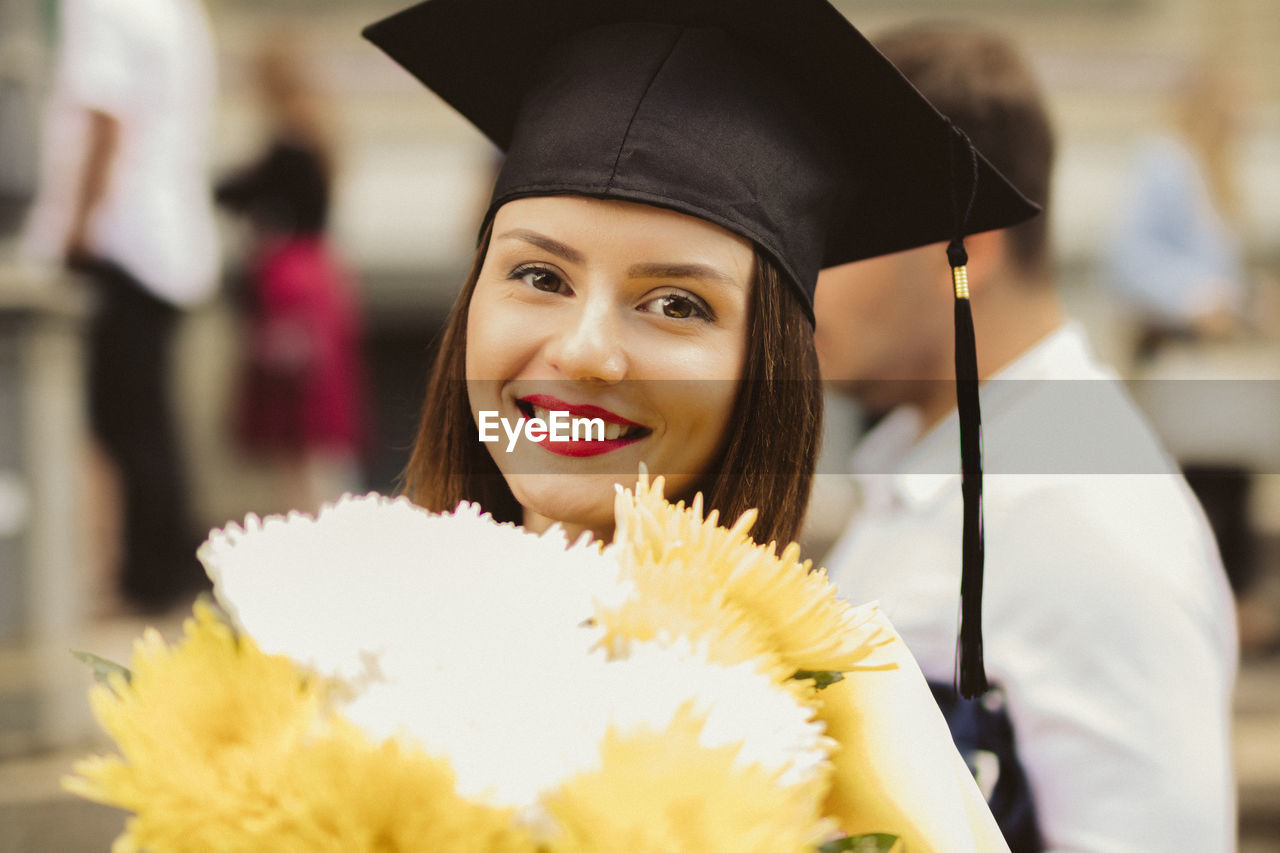 Portrait Of Smiling Young Woman With Mortarboard And Bouquet