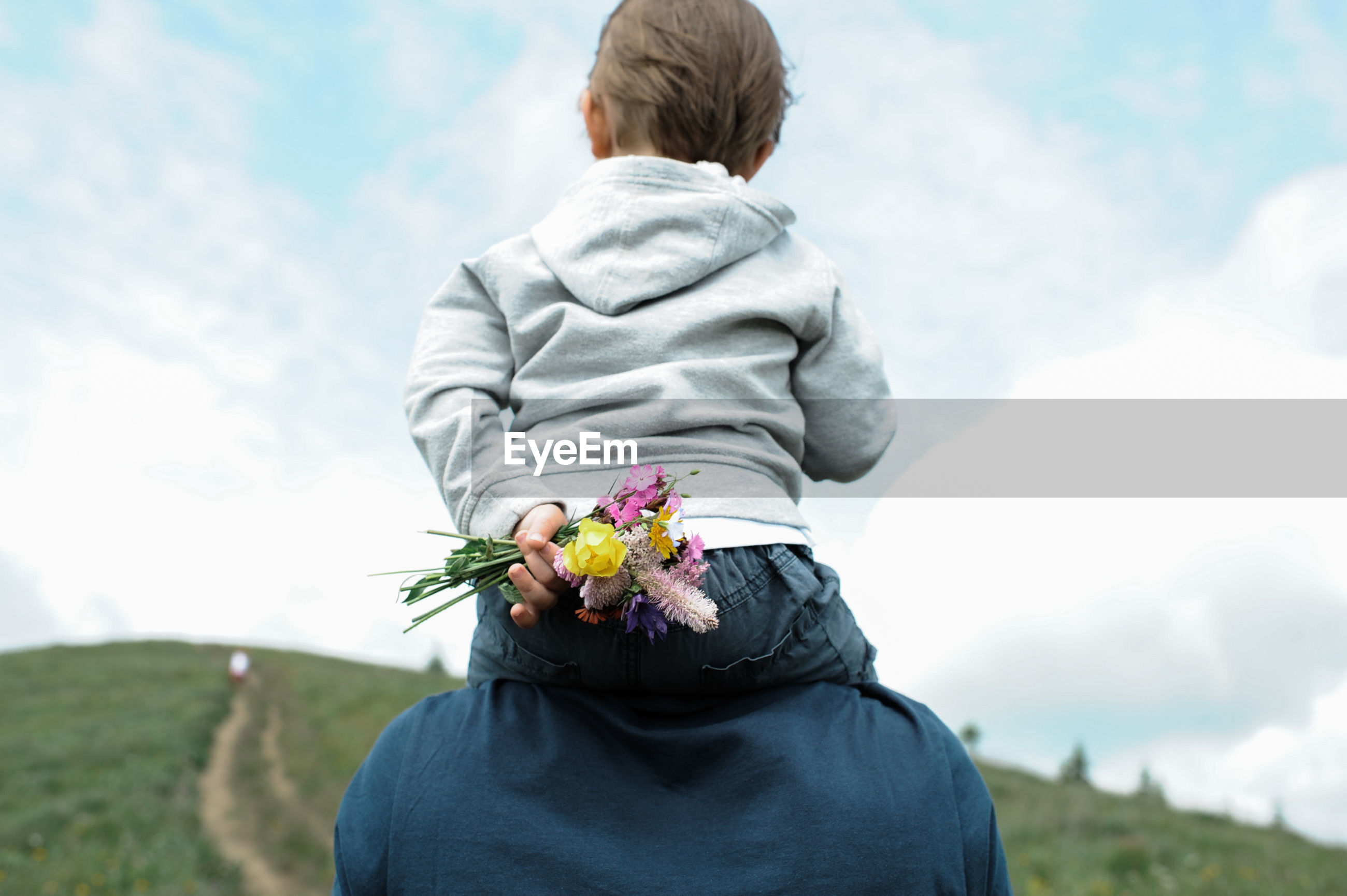 Rear view of father carrying son on shoulders