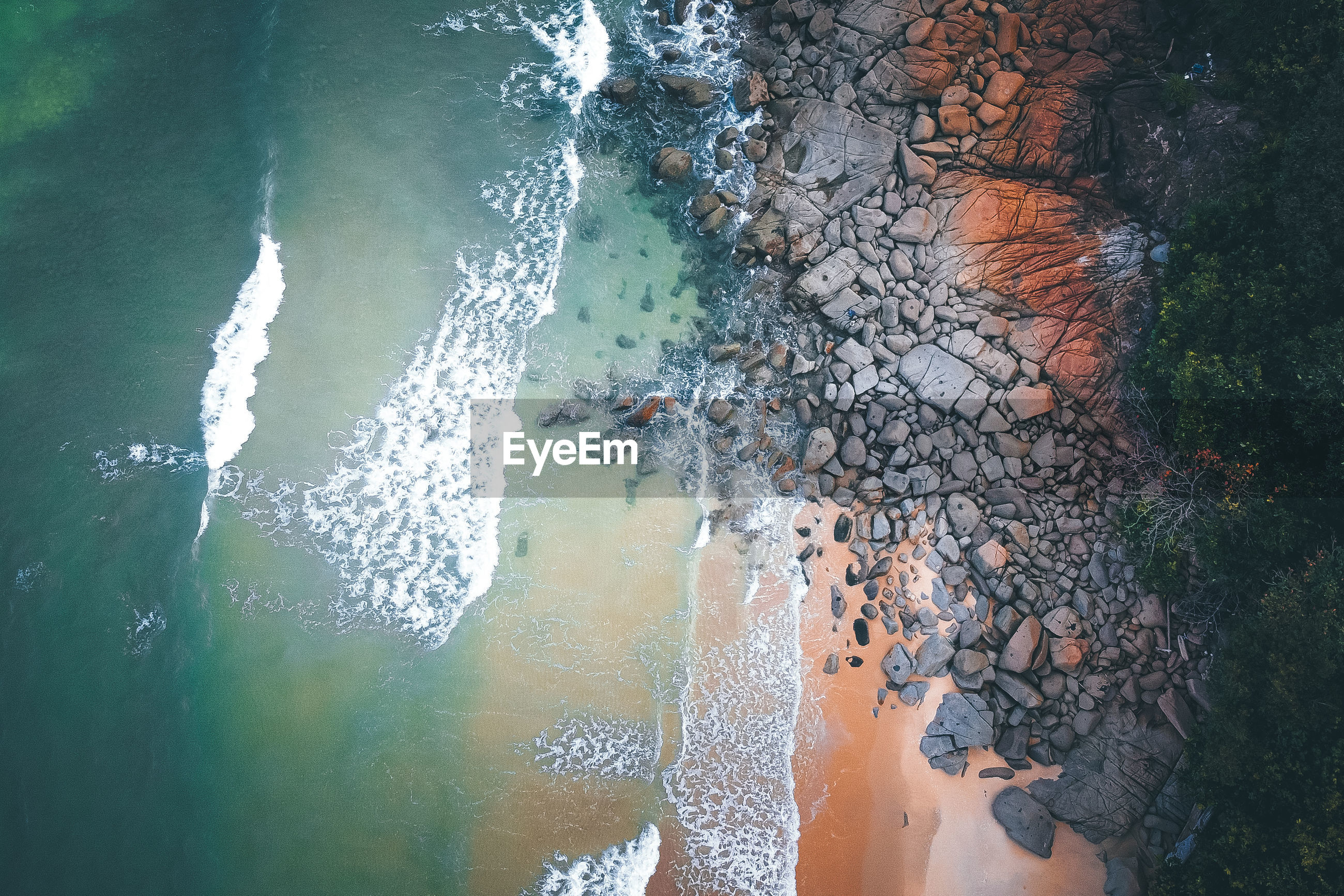 HIGH ANGLE VIEW OF WATER FALLING ON BEACH