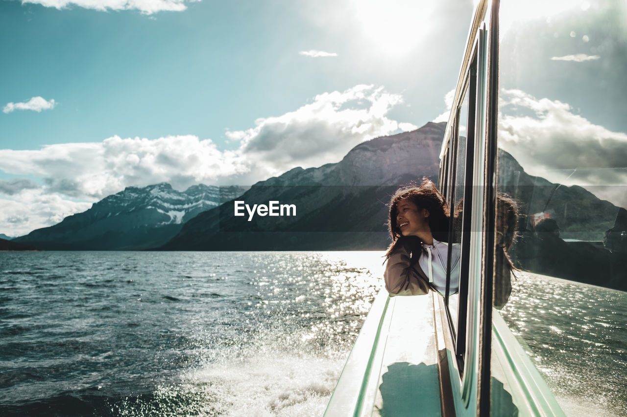 Young Woman Looking Through Ferry Boat Window In Sea